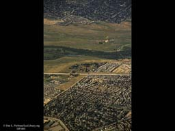 Urbanization closing in on river (aerial), Western USA